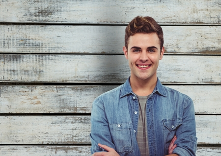 cross legged: Digital composite of Handsome man smiling against wooden wall Stock Photo