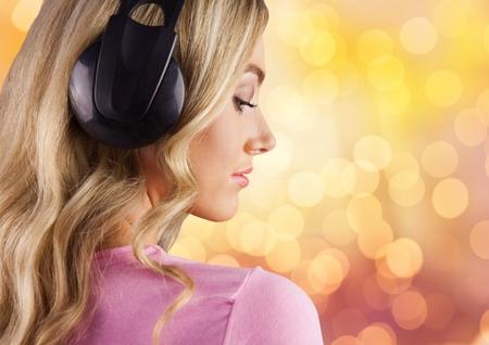 medical distribution: Digital composite of Woman wearing headphones over bokeh