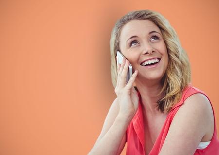 Digital composite of Happy woman using smart phone against orange background