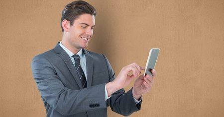 using smart phone: Digital composite of Smiling businesswoman using smart phone against brown background