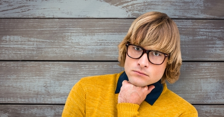 Digital composite of Male hipster wearing eyeglasses against wooden wall Stock Photo