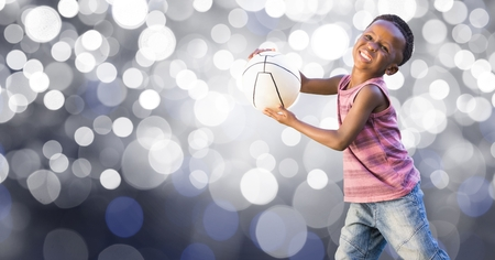Digital composite of Happy kid playing with ball over bokeh Stock Photo
