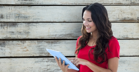 woman cellphone: Digital composite of Smiling woman using digital tablet against wooden wall Stock Photo