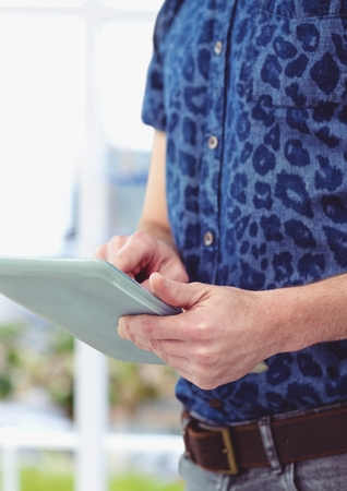 Digital composite of Midsection of male hipster using digital tablet against blurred background Stock Photo
