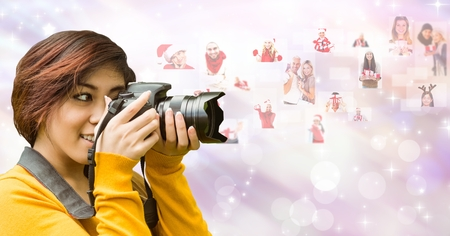 Digital composite of Female photographer using SLR camera by flying Christmas portraits Stock Photo