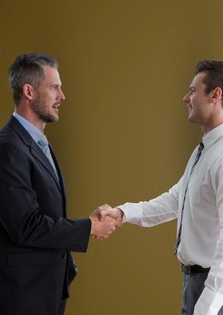 using tablet: Digital composite of Side view of businessmen shaking hands against green background