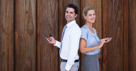 Digital composite of Smiling business people holding smart phone while standing back to back against wooden wall Stock Photo