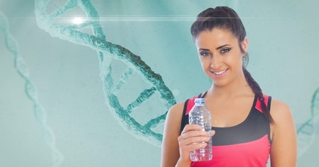 Digital composite of Fit young woman holding water bottle with DNA structure in background