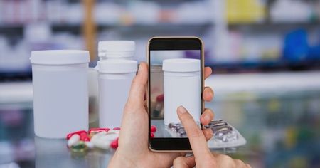 Digital composite of Hand photographing medicines on smart phone in pharmacy Stock Photo