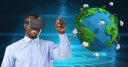computer animation: Digital composite of Smiling businessman wearing VR glasses by low poly earth Stock Photo