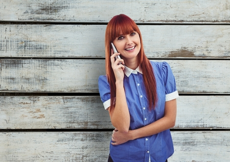 phoning: Digital composite of Redhead woman using mobile phone over wooden wall