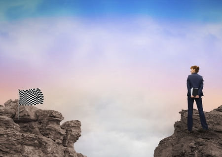 reach out: Digital composite of Rear view of businesswoman and checker flag on rocky mountains