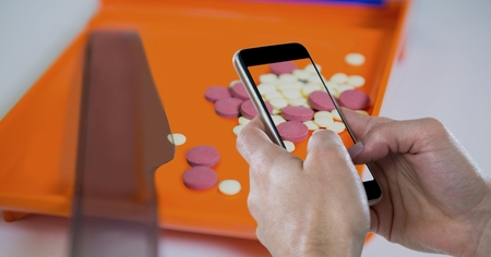 Digital composite of Hands photographing tablets through smart phone