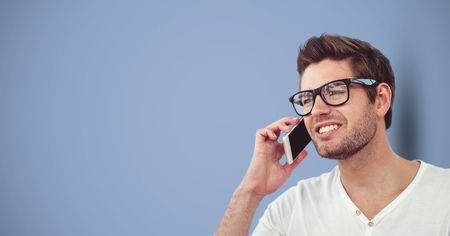 Digital composite of Male hipster using smart phone against blue background Stock Photo