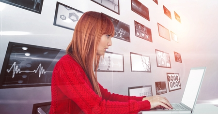 taken: Digital composite of Female hacker using laptop against screens Stock Photo