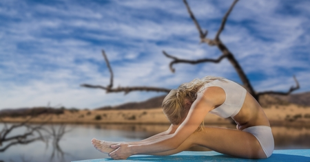 Digital composite of Double exposure of woman performing yoga by lake