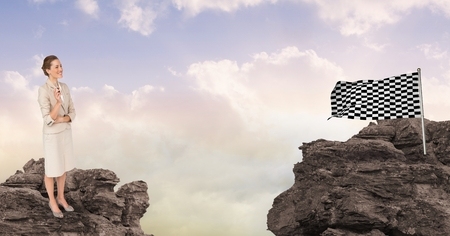 Digital composite of Businesswoman with checker flag on rocks Stock Photo