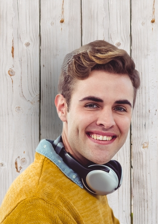 man holding transparent: Digital composite of Young man with headphones over wooden wall