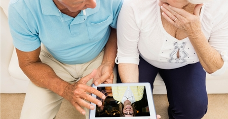 Digital composite of Senior couple video conferencing on tablet PC