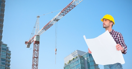 Digital composite of Low angle view of architect holding blueprint by crane