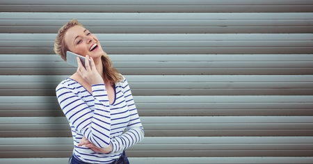 Digital composite of Happy woman using mobile phone against wall