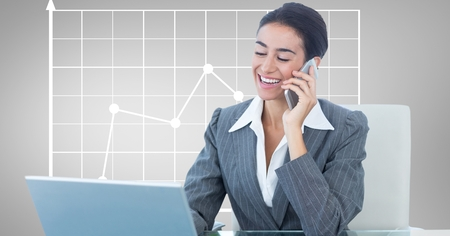 Digital composite of Happy businesswoman using laptop and mobile phone against graph