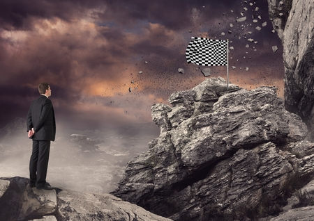 Digital composite of Businessman looking at checked flag on rock Stock Photo