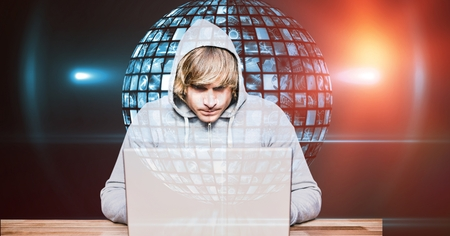 Digital composite of Hacker using laptop against globe Stock Photo