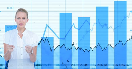 Digital composite of Angry businesswoman standing against graphs Stock Photo