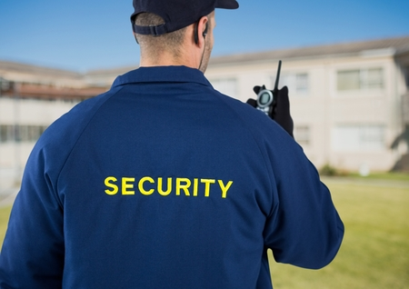 earpiece: Digital composite of Rear view of security guard using radio against house