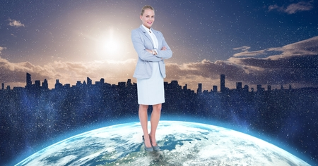 Digital composite of Businesswoman standing on globe against city Stock Photo