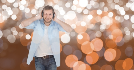 Digital composite of Smiling man listening to music on headphones against bokeh