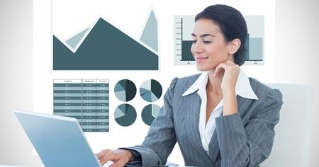 Digital composite of Confident businesswoman using laptop against graph background