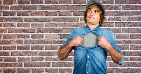Digital composite of Hipster tearing shirt against brick wall Stock Photo