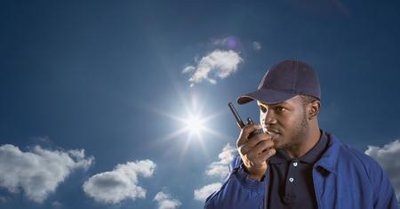 Digital composite of Security guard using radio against sky