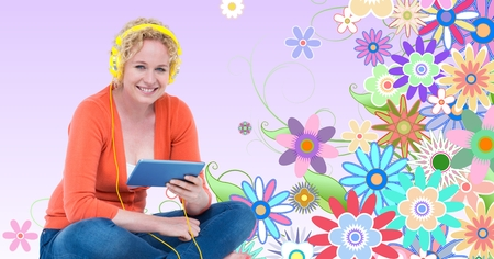 Digital composite of Smiling woman listening to music on headphones using tablet PC against floral background