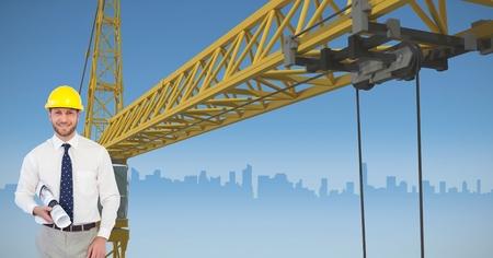 Digital composite of Architect holding blueprint against crane Stock Photo