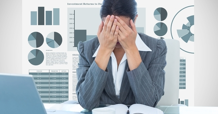 Digital composite of Stressed businesswoman covering face with hands against graphs