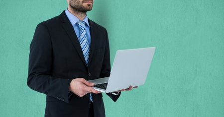 camaraderie: Digital composite of Midsection of businessman holding laptop over colored background