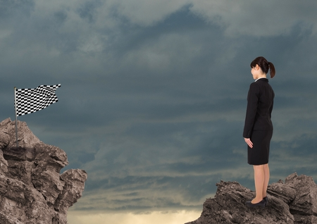 Digital composite of Businesswoman looking at checked flag against sky
