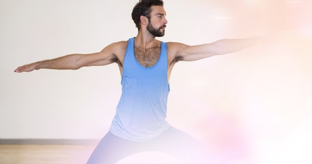 Digital composite of Young man performing yoga in gym