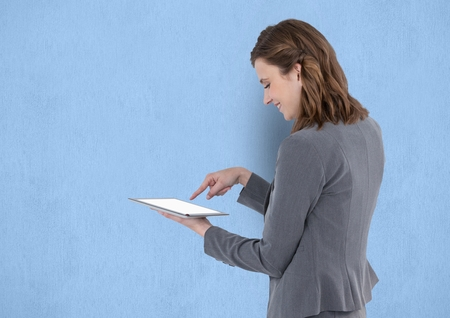 Digital composite of Businesswoman touching on blank screen of tablet PC over blue background