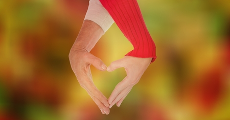 virtual reality simulator: Digital composite of Cropped image of couple making heart shape with hands against bokeh