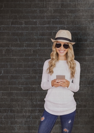 Digital composite of Smiling woman wearing sunhat and sunglasses while using smart phone