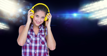 Digital composite of Smiling woman listening to music on headphones Stock Photo