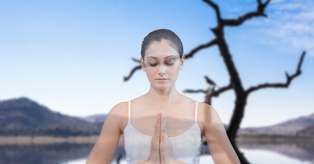 Digital composite of Double exposure of woman meditating with lake in background