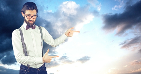 Digital composite of Male hipster pointing against cloudy sky