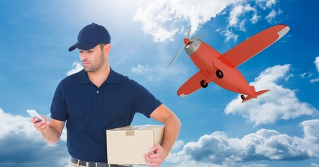Digital composite of Delivery man using mobile phone while holding parcel against airplane flying in sky Banco de Imagens