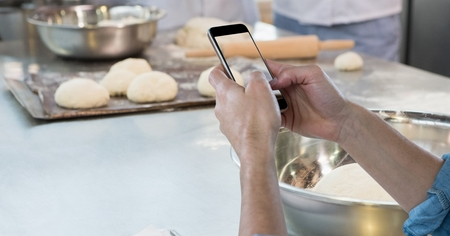 Digital composite of Hands photographing dough on smart phone Stock Photo