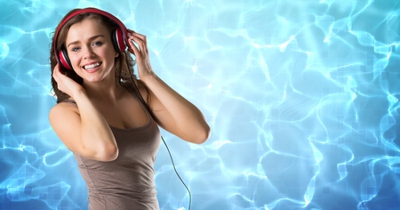 Digital composite of Happy woman listening music on headphones against reflection of sunlight in water Stock Photo